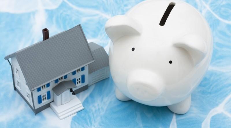 Un petit cochon tirelire à côté d'un petit jouer en forme de maison représentent le gain ou l'économie de trésorerie qu'amène un rachat de crédit hypothécaire réussi grâce à une simulation en ligne.