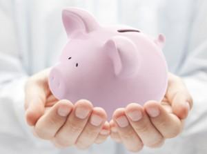 Deux mains tiennent une tirelire en forme de cochon rose, symbole classique d'une économie de sous.