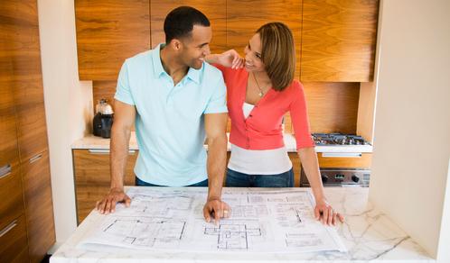 Un couple regarde les plans de leur nouvelle maison acquise grâce à un rachat de credit immo.
