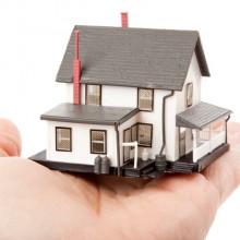 L'image représente une petite maison dans la paume d'une main ouverte, symbole du rachat credit immobilier sur notre site.