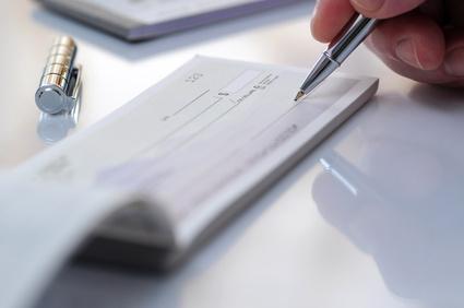 Un homme signe un chèque de frais de dossier représentant sa tentative de renégocier son prêt immobilier avec sa banque